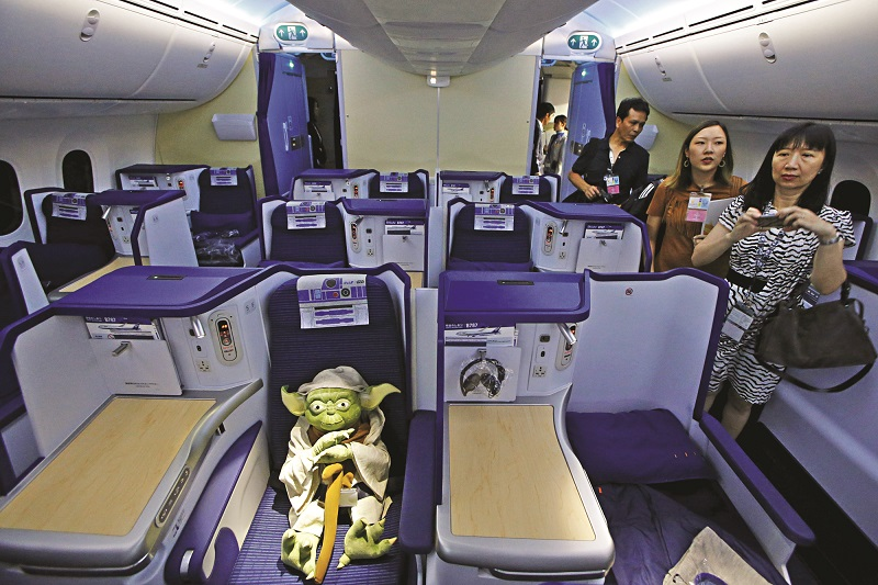 Visitors look at a Yoda plush toy sitting in the business class section during a tour of the Star Wars themed All Nippon Airways ANA R2D2 Boeing 787 Dreamliner aircraft in Singapore's Changi Airport November 12, 2015. The aircraft was open to the media on Thursday as it makes its first Asian stop outside Japan. REUTERS/Edgar Su  - RTS6KTN